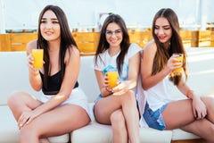 3 женщины выпивают коктеиль ослабленный и настроение потехи на призвании курорта лета на море Стоковые Изображения RF