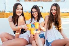 3 женщины выпивают коктеиль ослабленный и настроение потехи на призвании курорта лета на море Стоковые Фотографии RF