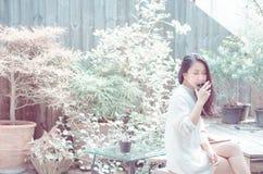 Женщины выпивают кофе в саде утра стоковое изображение