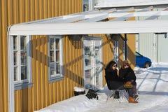 Женщины выпивают кофе перед старым деревянным домом в Tromso, Норвегии Стоковые Изображения RF