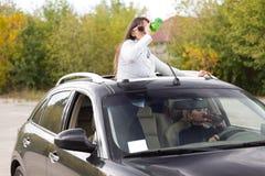 2 женщины выпивая и управляя Стоковая Фотография