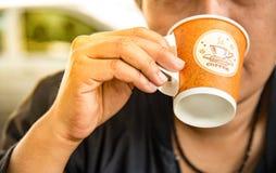 Женщины выпивая кофе в бумажном стаканчике во время путешествовать Стоковое фото RF