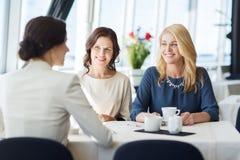 Женщины выпивая кофе и говоря на ресторане Стоковое фото RF