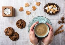 Женщины выпивая кофе с молоком и есть взгляд сверху печений Стоковые Фото