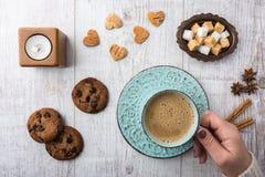 Женщины выпивая кофе с молоком и есть взгляд сверху печений Стоковое Изображение