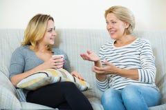 2 женщины выпивая чай и говоря на отечественном интерьере Стоковые Изображения