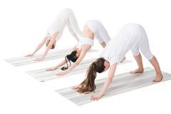Женщины выполняя йогу представляют на циновках йоги изолированных на белизне Стоковые Фото