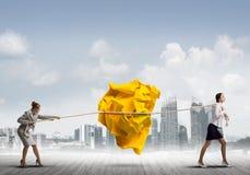 2 женщины вытягивая с шариком усилия большим скомканным бумаги как творческие способности подписывают Стоковая Фотография RF