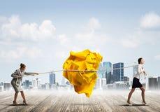 2 женщины вытягивая с шариком усилия большим скомканным бумаги как творческие способности подписывают Стоковые Фотографии RF