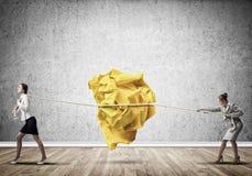 2 женщины вытягивая с шариком усилия большим скомканным бумаги как творческие способности подписывают Стоковое Изображение RF