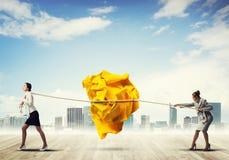 2 женщины вытягивая с шариком усилия большим скомканным бумаги как творческие способности подписывают Стоковые Изображения