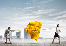 2 женщины вытягивая с шариком усилия большим скомканным бумаги как творческие способности подписывают Стоковая Фотография