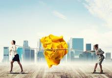 2 женщины вытягивая с шариком усилия большим скомканным бумаги как творческие способности подписывают Стоковые Фото