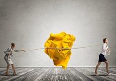 2 женщины вытягивая с шариком усилия большим скомканным бумаги как творческие способности подписывают Стоковое фото RF