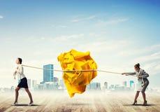 2 женщины вытягивая с шариком усилия большим скомканным бумаги как творческие способности подписывают Стоковое Фото