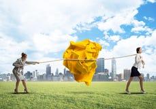 2 женщины вытягивая с шариком усилия большим скомканным бумаги как творческие способности подписывают Стоковое Изображение