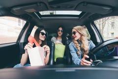 3 женщины в автомобиле имеют потеху после ходить по магазинам и продаж Стоковые Изображения