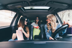 3 женщины в автомобиле имеют потеху после ходить по магазинам и продаж Стоковое фото RF