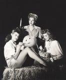 3 женщины в амбаре высекая тыквы на ноче Стоковая Фотография RF