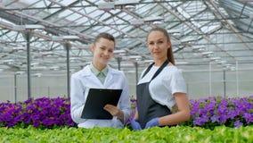 2 женщины в белых пальто и черных рисбермах Ученые, биологи или agronomists рассматривают и анализируют цветки и зеленый цвет акции видеоматериалы