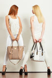 2 женщины в белых одеждах с сумками сумок Стоковая Фотография