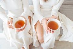2 женщины в белых платьях держа чашки чаю Стоковые Фотографии RF