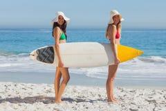2 женщины в бикини держа surfboard Стоковое Изображение RF