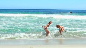 2 женщины в бикини играя в море видеоматериал