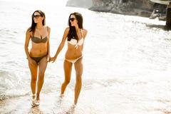 Женщины в бикини имея потеху на пляже Стоковое фото RF