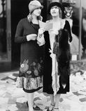 2 женщины в бумагах чтения улицы будучи бросанным вниз от офиса (все показанные люди нет более длинные живущих и никакого имущест Стоковое фото RF
