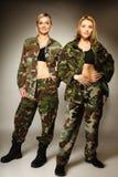 2 женщины в войсках одевают девушек армии Стоковое фото RF