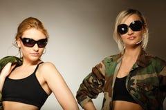 2 женщины в войсках одевают девушек армии Стоковая Фотография