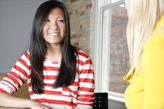 2 женщины в встрече команды с предпосылкой размеров офиса кирпича Стоковое Фото