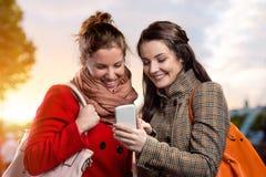 2 женщины в зиме покрывают с телефоном в солнечном парке Стоковое Изображение