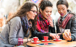 Женщины в кафе показывая изображения на умном телефоне Стоковое Изображение