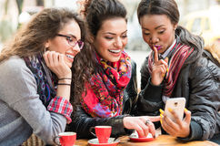 Женщины в кафе показывая изображения на умном телефоне Стоковые Фотографии RF