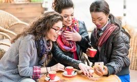 Женщины в кафе показывая изображения на умном телефоне Стоковое Фото