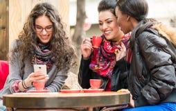 Женщины в кафе показывая изображения на умном телефоне Стоковая Фотография RF
