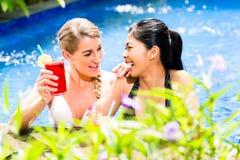 Женщины в коктеилях азиатского бассейна гостиницы выпивая Стоковая Фотография
