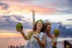2 женщины в костюмах греческих богинь на предпосылке красивого захода солнца на Ipanema приставают к берегу, Carnaval Стоковое фото RF
