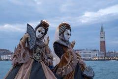 2 женщины в костюмах и маски, с украшенными вентиляторами, на Сан Giorgio, с квадратом меток St и колокольней позади Стоковое Изображение