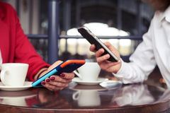 2 женщины в костюмах работая в smartphones и выпивая кофе Стоковые Изображения RF