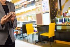 Женщины в кофейне используя мобильный телефон Стоковое Фото