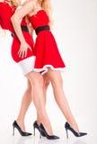 2 женщины в красном Санта Клаусе одевают с привлекательными ногами Стоковое фото RF