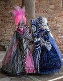2 женщины в красочных костюмах стоя рядом с старым каменным столбцом во время масленицы Венеции Стоковая Фотография RF