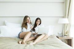 Женщины в кровати с компьтер-книжкой Стоковое Изображение RF