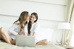 Женщины в кровати с компьтер-книжкой Стоковое фото RF