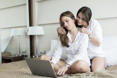 Женщины в кровати с компьтер-книжкой Стоковые Изображения RF
