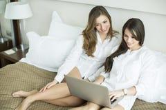 Женщины в кровати с компьтер-книжкой Стоковые Фотографии RF
