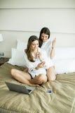 Женщины в кровати с мобильным телефоном nad компьтер-книжки Стоковая Фотография RF